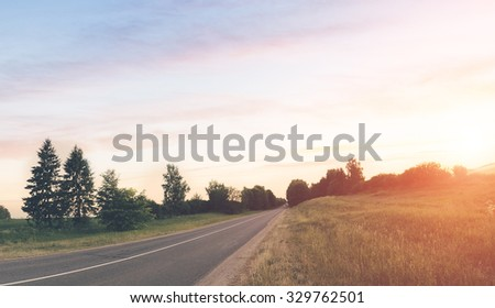 Beautiful landscape in summer time of the sunset on the village road - stock photo