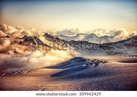 Beautiful landscape - mountain ridge of Western Caucasus in clouds at sunset or sunrise