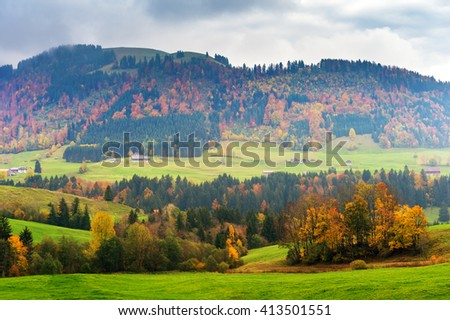 Beautiful landscape of a countryside with autumn trees in Alps - stock photo