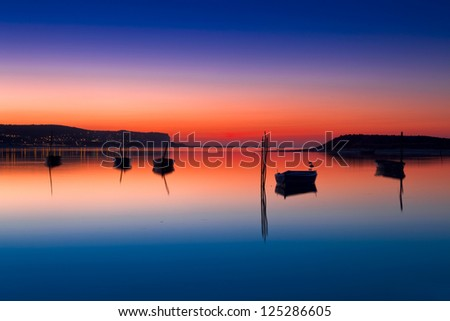 Beautiful landscape of a river and boats at sunset - stock photo