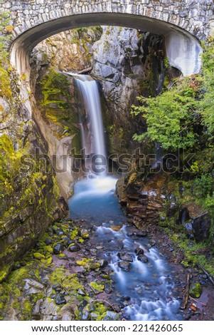 Beautiful landscape of a waterfall cascading down under a bridge - stock photo