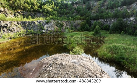 Beautiful landscape of abandoned and flooded quarry with shallow water and water plants, Czech Republic,