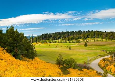Beautiful landscape of Llao Llao Hotel golf field with flowered hill in Villa la Angostura Patagonia Argentina - stock photo