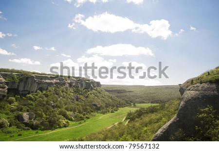 Beautiful landscape of mountains and fields of grass in a shiny weather - stock photo