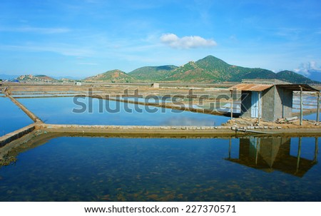 Beautiful landscape of salina filed on day under blue sky, store house reflect on saltwater, chain of mountain behind, amazing scene of agriculture at Vietnamese countryside
