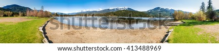 Beautiful landscape of the Alta Lake in Rainbow Park, Whistler, Canada, with wooden peer in the foreground and snow-covered mountains in the background - stock photo