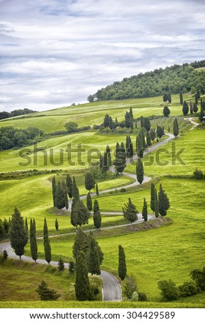 Beautiful landscape of Tuscany with the twisting road and cypresses - stock photo
