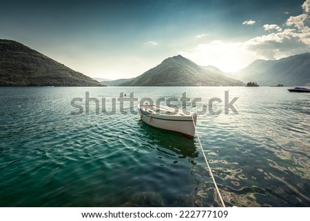 Beautiful landscape of white rowboat moored at bay surrounded by mountains at early morning - stock photo