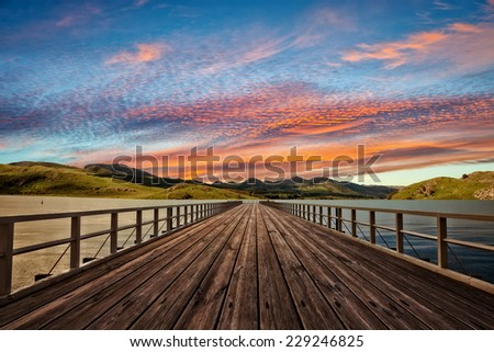 Beautiful landscape on the lake with wooden pier in the mountains in the background.  - stock photo
