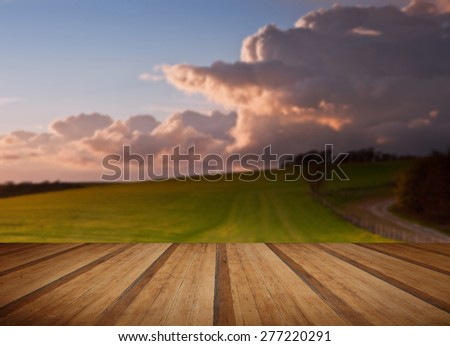 Beautiful landscape over agricultural fields with moody sky with wooden planks floor - stock photo