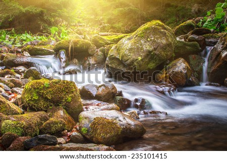 Beautiful landscape rapids on a mountains river in sunlight. Filtered image: colorful effect.  - stock photo
