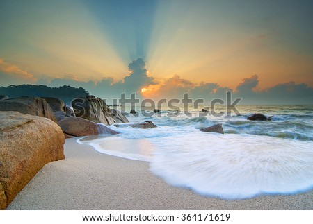 Beautiful landscape sunrise in the sea with stones on a long exposure. Soft Focus due to Long Exposure Shot - stock photo