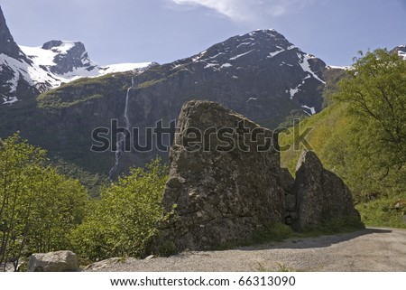 Beautiful Landscape taken at Briksdale, Norway. With Large Boulder in foreground an snow capped mountains in Background.