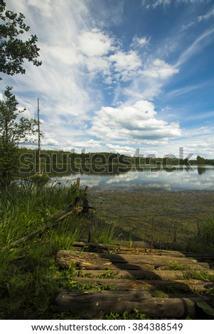 Beautiful landscape with a lake. the mirror surface of the water reflects the blue sky - stock photo