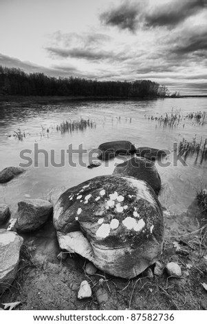 Beautiful landscape with big stone in the foreground. Black and white photography.