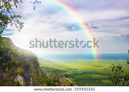 beautiful landscape with cloudy blue sky and rainbow - stock photo