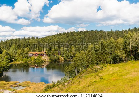 Beautiful landscape with cottage near a lake and trees