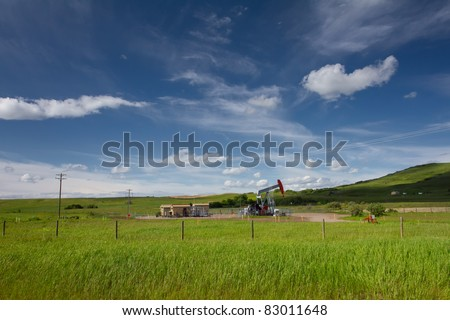 Beautiful landscape with green grass, blue sky and pumpjack. Photo is taken on sunny day of summer in Alberta, Canada. - stock photo