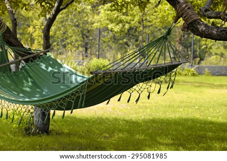 Beautiful landscape with hammock in the summer garden, sunny day. Selective focus - stock photo
