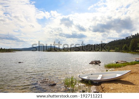 Beautiful landscape with lake shore, stones and pines - stock photo