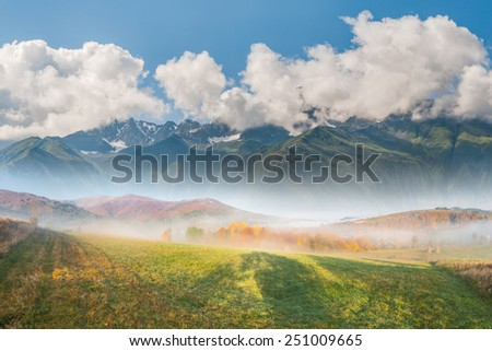 Beautiful landscape with meadow, mountain, fog and clouds - stock photo
