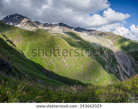 Beautiful landscape with mountain peaks and meadows - stock photo