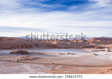 Beautiful landscape with red rocks, clouds and blue sky at Valle de La Luna during sunset - stock photo