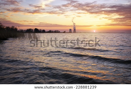 Beautiful landscape with reservoir, sunset sky and power plant.  - stock photo
