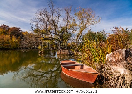 Beautiful landscape with river and red boat near the shore