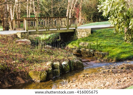 Beautiful landscaped garden with a wooden bridge to walk over and a creek with running water underneath it.  - stock photo