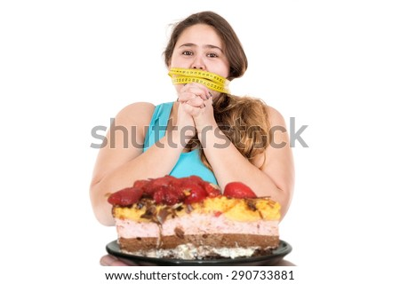 Beautiful large girl gagged with measuring tape looking at a cake isolated in white - stock photo