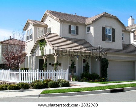 Beautiful large home with white picket fence. Blue sky with wispy clouds. - stock photo