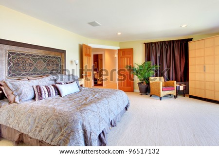 Beautiful large master bedroom with grey bed and chair.