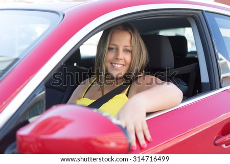 Beautiful large woman driving a red sports car