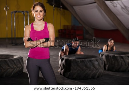 Beautiful Latin brunette greeting customers with a smile to a cross-training gym - stock photo