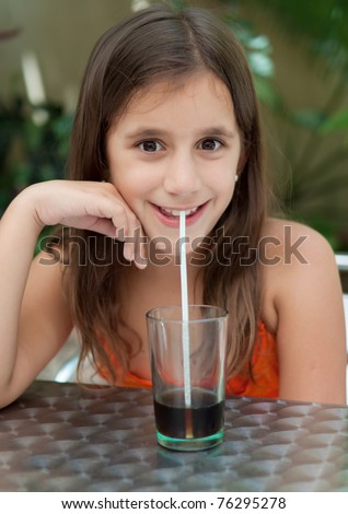 Beautiful latin girl drinking soda with a straw in an outdoors cafeteria - stock photo