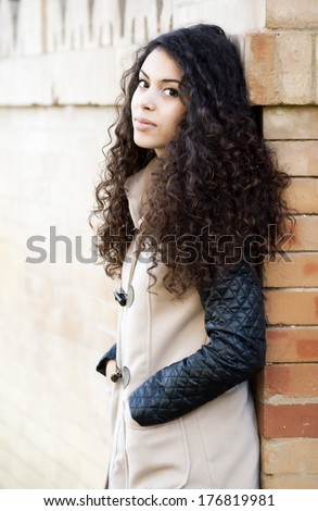 Beautiful  Latin Girl leaning against a wall in the park - stock photo