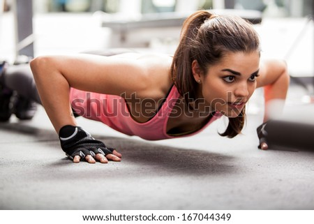 Beautiful Latin woman doing push ups in the gym before lifting some weights - stock photo