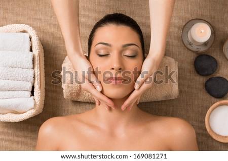 Beautiful Latin Woman Getting Facial Massage At Spa - stock photo