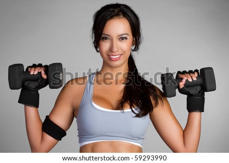 Beautiful latin woman lifting weights - stock photo