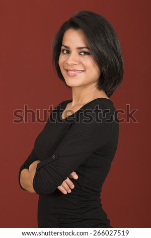 Beautiful latin woman smiling with her arms crossed isolated over a red background - stock photo