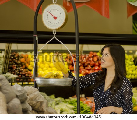 Beautiful latin woman weighing fruits on a scale in a supermarket - stock photo