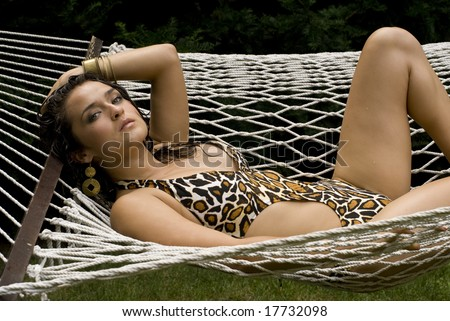 Beautiful Latina in animal print bathing suit laying in a white hammock on a sunny day