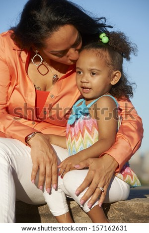 Beautiful Latina Mother and toddler girl sitting in urban park in front on New York City skyline.