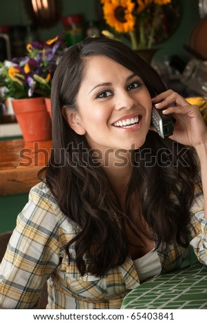 Beautiful Latina Woman at table in Kitchen on Phone - stock photo