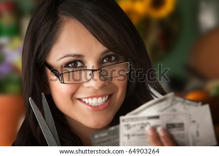 Beautiful Latina Woman at table in Kitchen with Coupons - stock photo