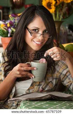Beautiful Latina Woman at table in Kitchen with Tea - stock photo