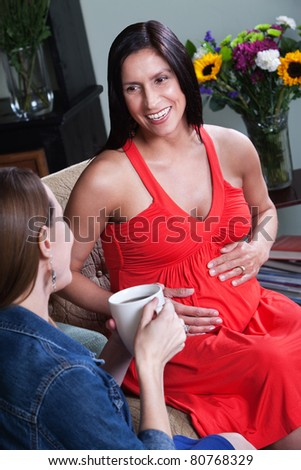 Beautiful Latina woman holds her belly with friend - stock photo