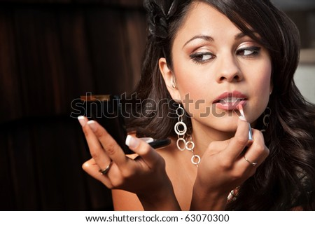 Beautiful Latina Woman Looking into Compact Mirror and Applying Lip Gloss - stock photo