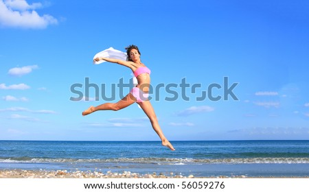 Beautiful latino woman jumping by the sea in Greece